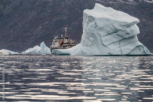 In de dag Poolcirkel expedition vessel surrounded by massive Icebergs floating in the fjord scoresby sund, east Greenland