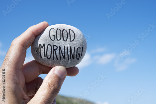 Fotografia  closeup of a young caucasian man showing a stone with the text good morning writ