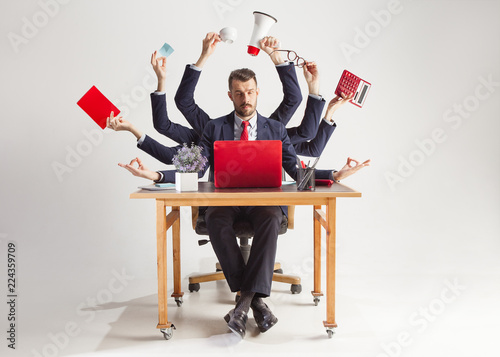 Fototapeta businessman with many hands in elegant suit working and holding office tools. Isolated over white background. Concept of busy obraz