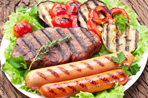 Grilled meat and vegetables over green leaves on white plate on the wooden table.