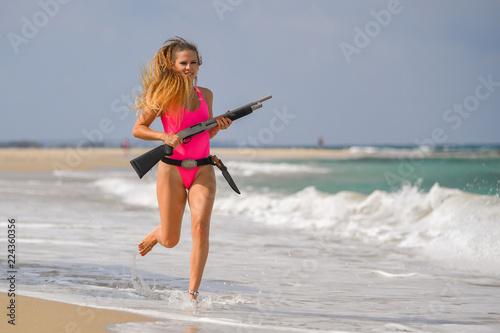 Obraz na płótnie Beautiful sexy girl in a swimsuit with a carbine runs along the seashore