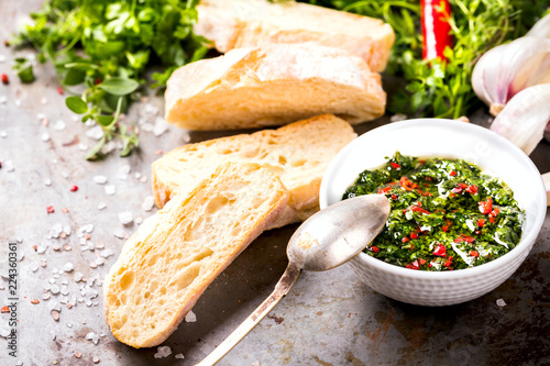 Argentinian green Chimichurri with ingredients.Raw homemade with ciabatta.Salsa or sauce made of parsley, garlic, oregano, hot pepper, olive oil, vinegar.Food Concept