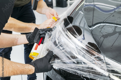 Photo Car wrapping specialist putting vinyl foil or film on car