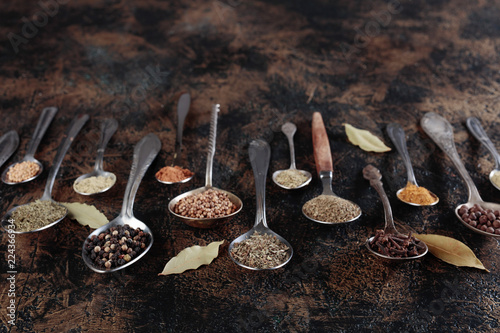 Different spices in spoons on a vintage background.