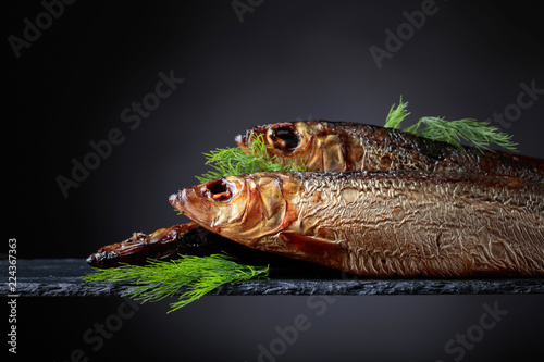 Smoked Baltic herring with dill on a black background.