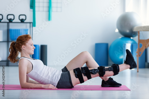 Sportswoman on mat doing exercises with broken leg during rehabilitation