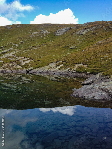 Fotografía  panoramic view of an alpine lake, where the Swiss mountains are mirrored at the Simplon pass