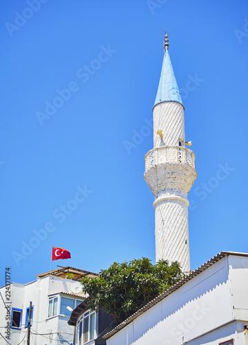 Fotografia  Minaret of Kelerlik Mahallesi Cami mosque with the flag of Turkey waving in foreground