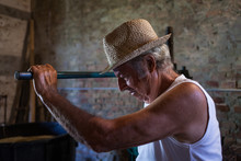 Portrait Of Old Winemaker Farmer Working On A Traditional Wine Press. Winery Background