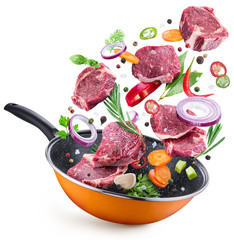 Obraz Flying meat steaks and spices over a frying pan. File contains clipping path.