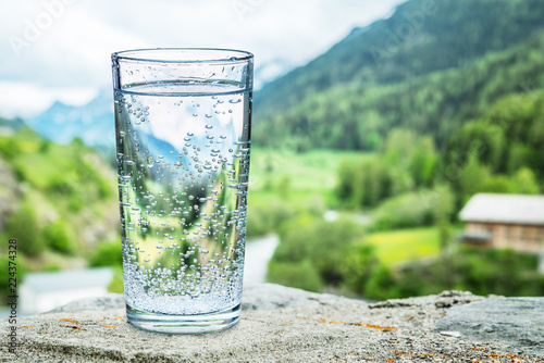 Foto op Plexiglas Water Glass of water on the stone. Blurred snow mountains tops and green forests at the background.