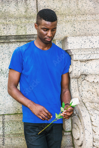 Lonely Young African American Man missing you in New York, wearing blue short sleeve T shirt, standing in corner of vintage wall on campus, holding white rose flower, looking down, sad, thinking..