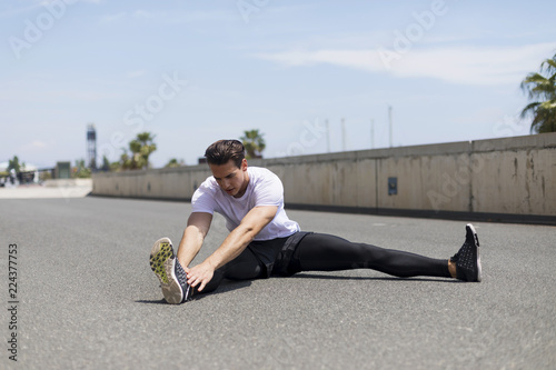Fototapety, obrazy: Muscular athlete working outdoors stretching his body