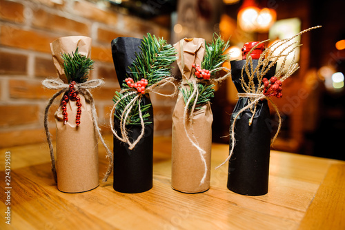 Four adorable christmas decorated bottles with ribbons and fir-tree branch