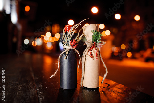 Two christmas decorated gift bottles standing on the wooden bench