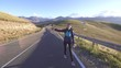 Girl tourist with backpack behind hitchhiking on the road