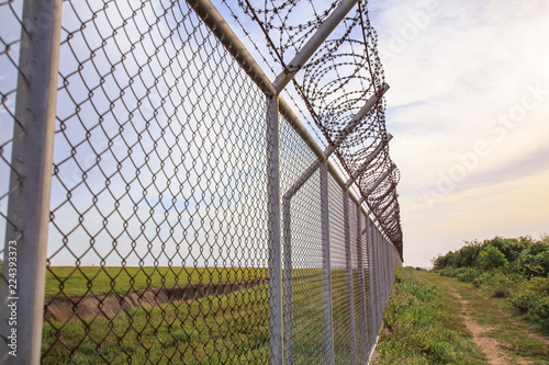 Chain link fence with grass field Phuket International