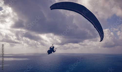Silhouette of a man flying on a paraglider high above the sea in the clouds, sport, beauty and freedom concept