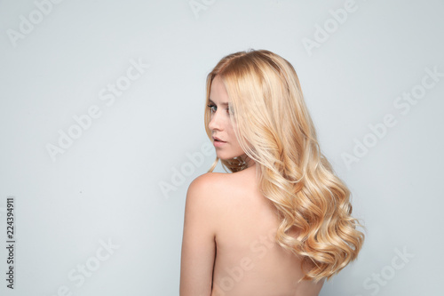 Deurstickers Akt Beautiful woman with healthy long blonde hair on light background