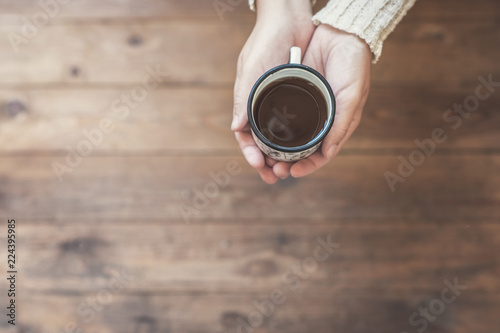 Staande foto Thee A girl in the winter knitted mittens with an iron mug of coffee on the wooden terrace. Winter concept