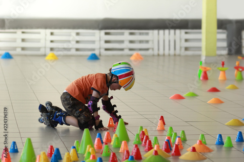 Cuadros en Lienzo  Boy building obstacles with pegs to learn slalom rollerskate tricks