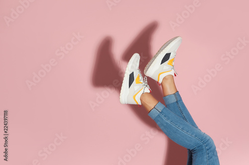Fototapeta Woman in stylish sneakers near color wall, closeup. Space for text obraz