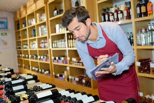 Wine merchant checking his stock Wallpaper Mural