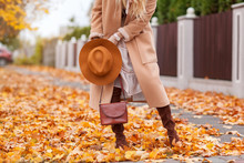A Beautiful Fashionable Woman Walks Through The Autumn Park In A Coat And A Hat With A Handbag In Her Hands Front View