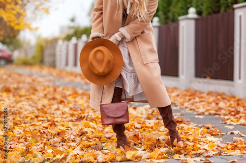 Fototapeta A beautiful fashionable woman walks through the autumn park in a coat and a hat with a handbag in her hands front view obraz