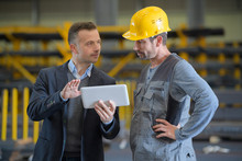 Men In Industrial Building Looking At Tablet