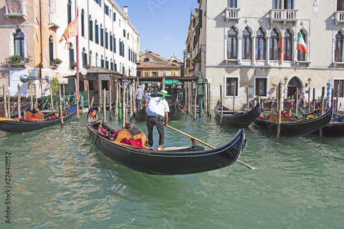 Foto op Aluminium Gondolas Venetian gondolier in the gondola is transported tourists through canal waters of Venice Italy