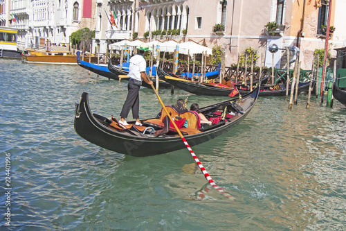 Poster Venetie Venetian gondolier in the gondola is transported tourists through canal waters of Venice Italy
