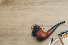 A Smoking Pipe With Tobacco, Pipe Tamper Tool, And Matches On Wooden Table