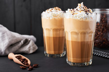 Iced Caramel Latte Coffee In A Tall Glass With Chocolate Syrup And Whipped Cream. Dark Wooden Background.