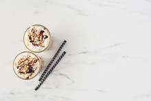 Top View Of Two Ice Coffee In A Tall Glass With Caramel And Chocolate Syrup On Whipped Cream And Two Straws. White Marble Background With Copy Space.