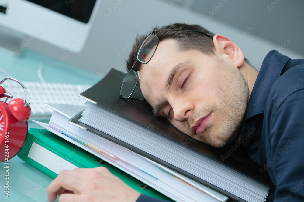 Fototapeta businessman in office asleep on stack of folders