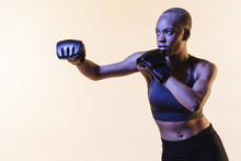 Pull A Punch, Portrait Of A Young Woman Boxing, Against A Blank Studio Background
