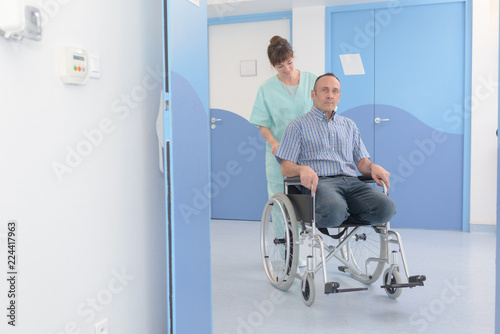 man being pushed in his wheelchair by nurse Canvas Print