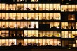Leinwanddruck Bild - Office building at night. Late night at work. Glass curtain wall office building