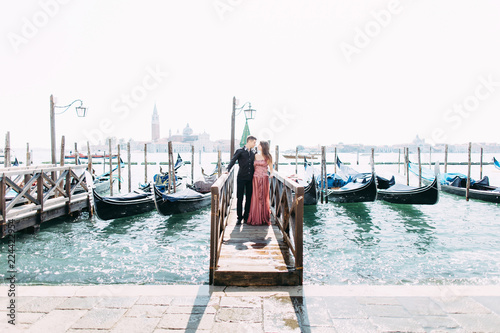 Foto op Aluminium Gondolas Romantic travel couple in Venice on Gondole ride romance in boat happy together on travel vacation holidays. Romantic young beautiful couple sailing in venetian canal in gondola. Italy, Europe.