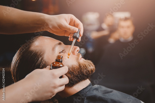 Fotografia Barber applies beard oil with dropper for man in barbarshop.