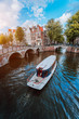 canvas print picture - Tour boat at famous Dutch canal on a sunny day, traditional Dutch bridges, medieval houses. Amsterdam Holland