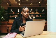 Portrait Of Businesswoman Holding Smartphone While Working On Laptop