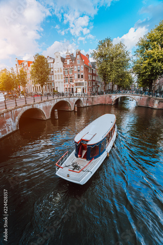 Tour boat at famous Dutch canal on a sunny day, traditional Dutch bridges, medieval houses Fotobehang
