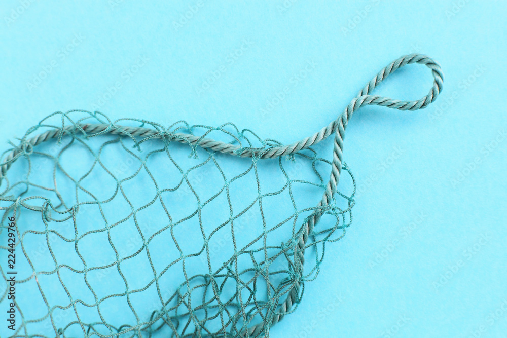 Fototapeta Fishing net with space for your text. Blue background for a fishery theme.
