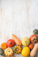 Assortment Of Pumpkins And Gourds On The White Wooden Tablebackground Arranged In A Grid, Copy Space For Text, Selective Focus