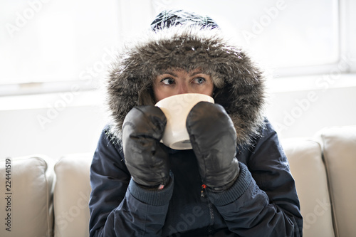 Fotografie, Tablou  Woman have cold drink coffee on the sofa at home with winter coat