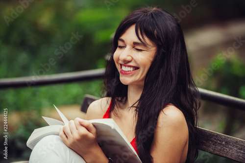 Fotografia, Obraz Beautiful smart woman reading a book and laughing in the green park outdoors