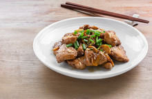 Stir Fried Chicken With Black Soy Sauce In A Ceramic Dish On Wooden Table. Asian Homemade Style Food Concept.