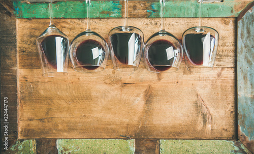 Foto Flat-lay of red wine in glasses in row over rustic wooden tray background, top view, copy space